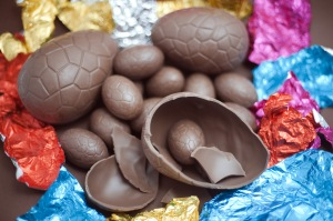 Opened chocolate Easter Eggs in a pile amongst their colourful foil wrappers with one large egg broken in half