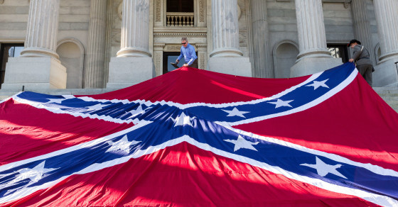 COLUMBIA, SC - MAY 02: Confederate re-enactors position a gigantic Confederate flag on the steps of the South Carolina State Capitol building on May 2, 2015 in Columbia, SC. Confederate Memorial Day is a official state holiday in South Carolina and honors those that served during the Civil War. (Photo by Richard Ellis/Getty Images)
