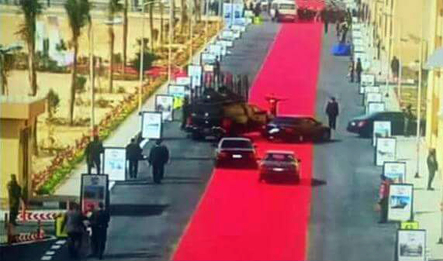 In this Saturday, Feb. 6, 2016 image taken from Egypt State TV, Egyptian President Abdel-Fattah el-Sissi's motorcade drives on a red carpet during a trip to open social housing projects in a suburb of Cairo, Egypt. Images of the giant red carpet prompted a wave of mockery on social media, and one local newspaper devoted its entire front page Monday, Feb. 8, 2016, to accusing el-Sissi of decadence while he asks Egyptians to tighten their belts. (Egypt State TV via AP)